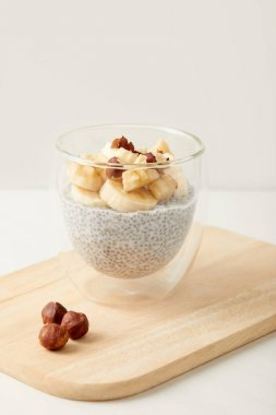 close up view of tasty chia seed pudding with pieces of banana and hazelnuts on wooden cutting board