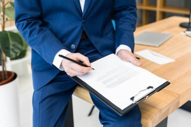 cropped shot of businessman with notepad and pen in hands at workplace in office