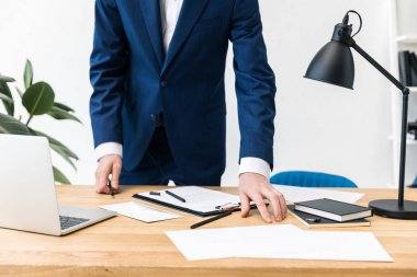 partial view of businessman in suit at workplace with notebooks, documents and laptop in office