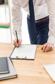 Fotografie partial view of businessman signing papers at workplace in office