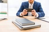 Fotografie částečný pohled podnikatel v obleku pomocí smartphone na pracovišti s notebooky v úřadu
