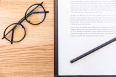 pohled shora brýle, tužka a Poznámkový blok s dokumenty o dřevěný povrch