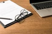 Fotografie zblízka pohled na brýle, laptop a Poznámkový blok s perem na dřevěnou desku