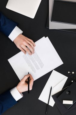partial view of businessman in suit signing papers at workplace with laptop