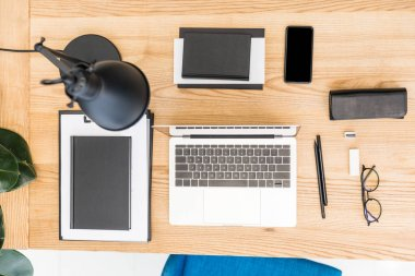 top view of arranged eyeglasses, laptop, notebooks and smartphone at workplace