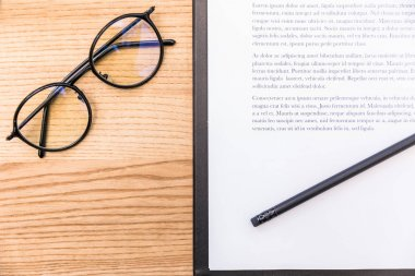 top view of eyeglasses, pencil and notepad with documents on wooden surface