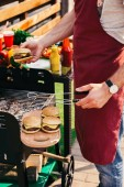 Fotografie Chef cooking hamburgers with cheese outdoors on grill
