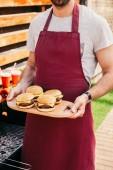 Close-Up Nézd ember tartó fedélzet-val hamburgert főtt szabadban, grill