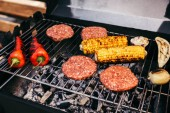 Fotografie Meat patties and vegetables cooked outdoors on grill