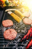 Grounded meat and corn cooked outdoors on grill