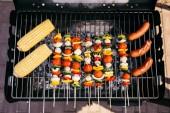 Salámy vařené venku na grilu s kukuřicí a zeleninou