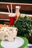 Fotografia Funghi in cestino e salsicce preparate per le grigliate allaperto