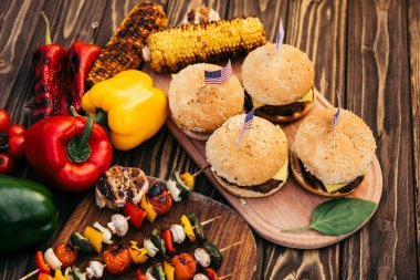 Independence day dinner with hamburgers and vegetables cooked outdoors on grill