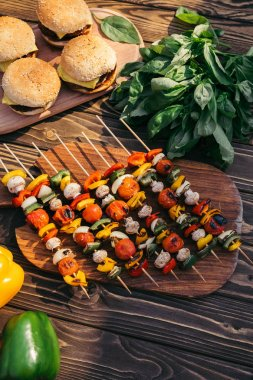 Vegetables on skewers and hamburgers cooked outdoors on grill