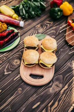 Cut vegetables and burgers grilled for outdoors barbecue