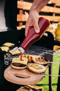 Man adding ketchup to burgers cooked outdoors on grill
