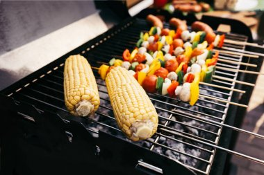 Corn cobs and vegetables on skewers cooked outdoors on grill