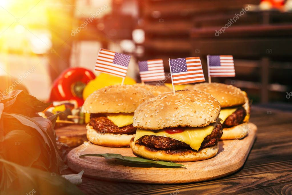 USA flags on hamburgers grilled for outdoors barbecue