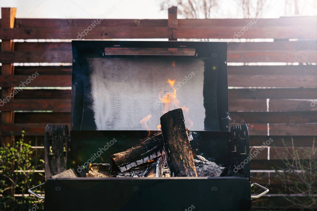 Logs burning in grill for barbecue outdoors