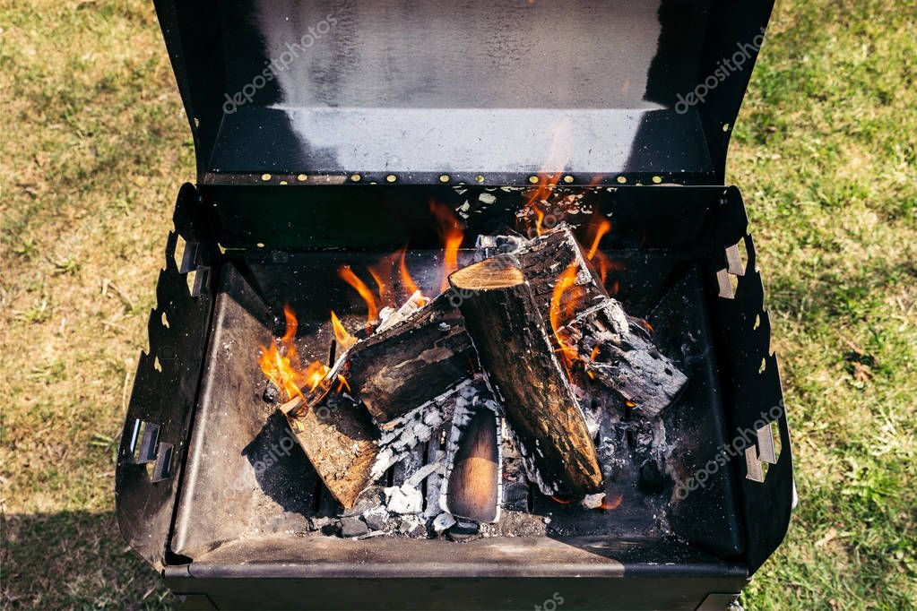 Outdoor grill with burning firewood for barbecue