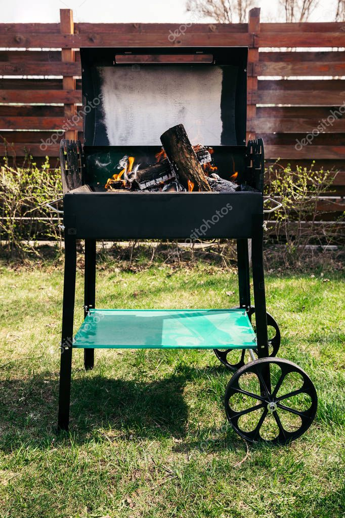 Metal outdoor grill with logs burning on fire