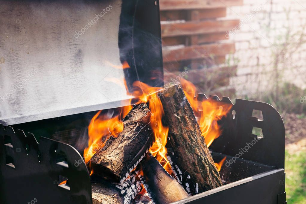 Fire over wooden logs in outdoors bbq