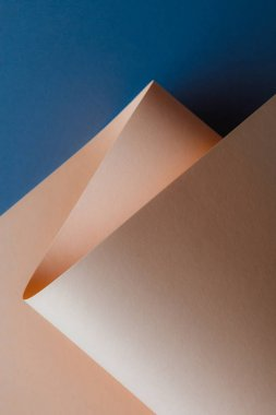 close-up view of beautiful tender beige paper sheet on dark blue background