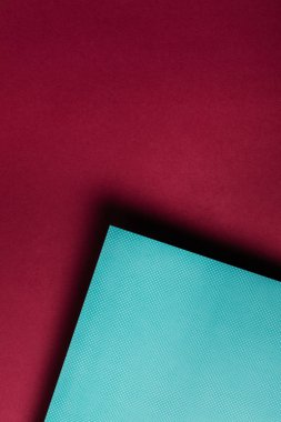 creative turquoise paper sheet on grungy maroon background
