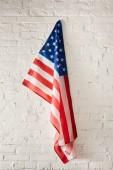 Photo united states of america flag hanging on white brick wall