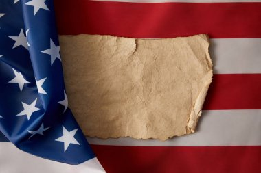 top view of blank vintage crumpled paper on american flag