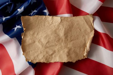 elevated view of vintage blank crumpled paper on american flag