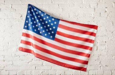 closeup shot of united states of america flag on white brick wall