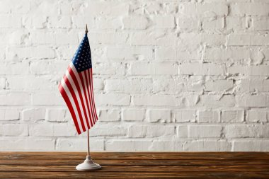 united states of america flagpole on wooden surface against brick wall