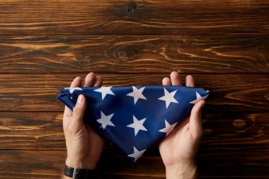 cropped shot of man holding folded american flag on wooden background