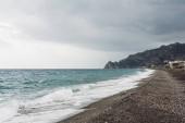 mořské vlny stříkající na písečné pláži v pobřeží