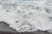 bílá mořská pěna na písečné pláži