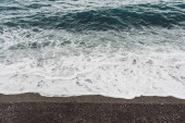 mořské vlny s bílou pěnou na písečné pláži v pobřeží