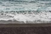 mořské vlny s bílou pěnou na pláži v pobřeží