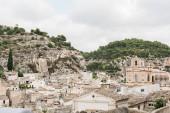 Scicli, Italia - 3 ottobre 2019: antica città italiana con casette e chiesa contro il cielo azzurro con le nuvole