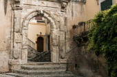 Photo ancient arch in old building near green plants in modica, italy