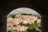 Photo arch near small houses and green trees in ragusa, italy