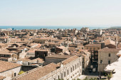 Photo sunlight on brown roofs of old houses near sea in catania, italy