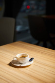 cup of hot coffee on wooden table in cafe