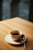 szelektív fókusz fehér csésze kávé közelében kanál kávézóban