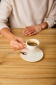 kivágott kilátás nő gazdaság csésze forró kávé kávézóban