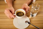 szelektív fókusz a nő kezében csésze kávét pohár víz mellett kávézóban
