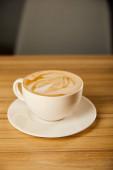 chutné cappuccino v bílém poháru s podšálkem na stole