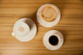 top view of saucers with white cups of tasty coffee in cafe