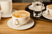selective focus of saucers with cups of tasty coffee in cafe