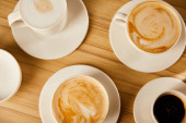 top view of saucers with cups of different coffee